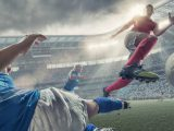 A cross processed mid action image of professional women soccer player in mid air jumping over a rival player who is performing a sliding tackle. The action takes place during a professional women's football game in a generic floodlit soccer stadium full of spectators under a stormy evening sky at sunset.